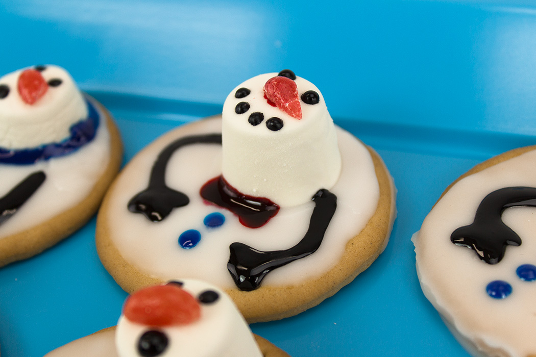 home-made cookies with a marshmallow and icing topping made to look like a snowman