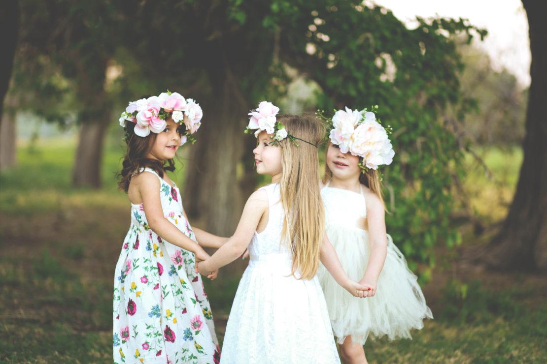 children girls holding hands in the garden