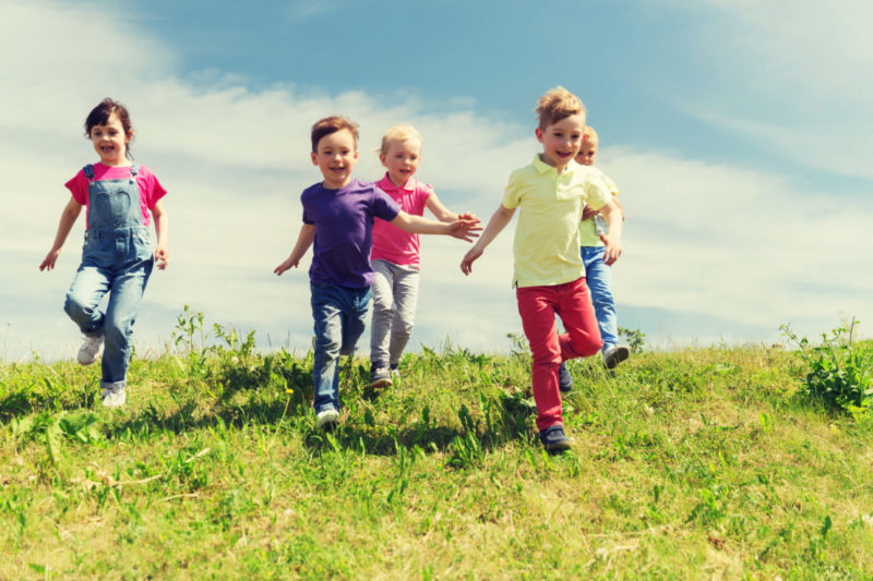 children running downhill together in a group on a sunny day