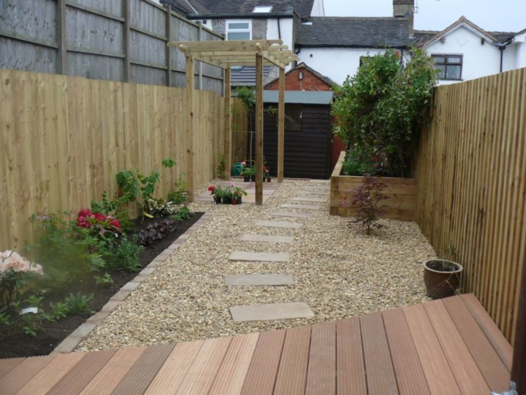 a narrow garden with a deck area and a paving stone pathway leading across gravel