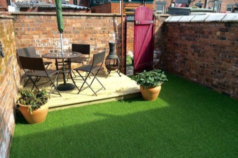 a small garden with deck area and artificial grass