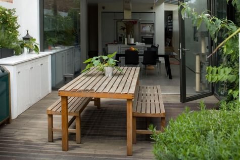 low-maintenance garden ideas with benches and a table on a deck