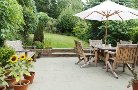 a set of wooden dining furniture on a garden patio