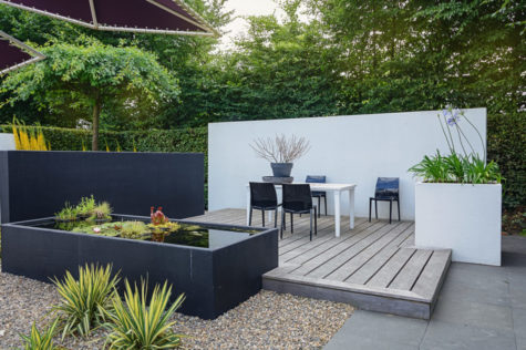 a stylish modern deck with plastic garden dining table and a rectangular pond with plants