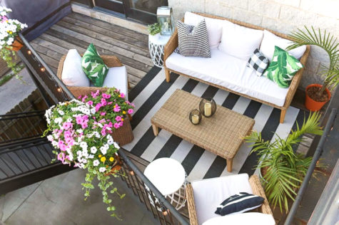 a top-down view of a small balcony with furniture, rigs and overflowing flowers