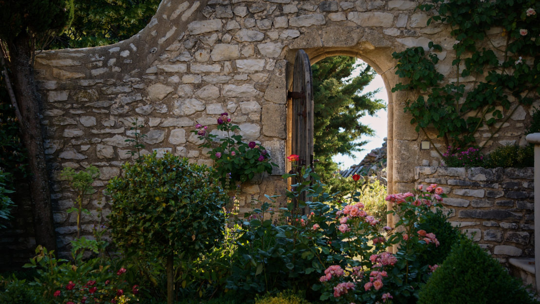 a stone wall with an open gate in a pretty enchanted garden