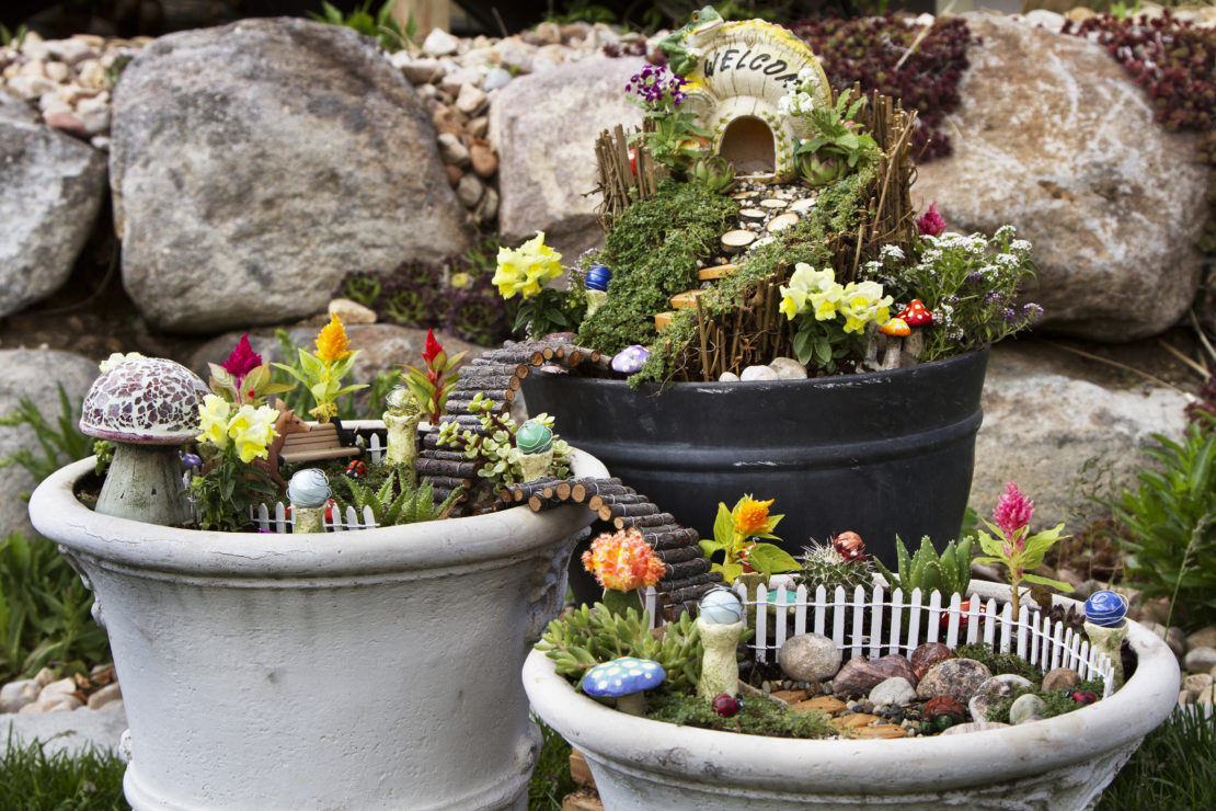 Three pots with miniature fences, flowers and doorways, creating fairy gardens
