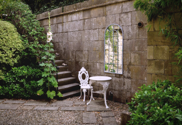 white patio furniture against a vine-covered wall with a mirror