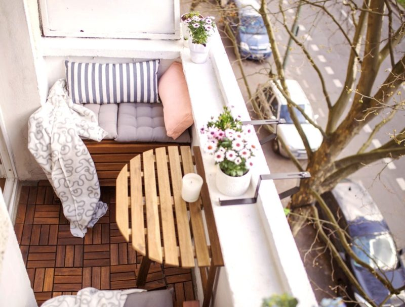 tiny balcony overlooking the street, with a folding table and wood floor tiles