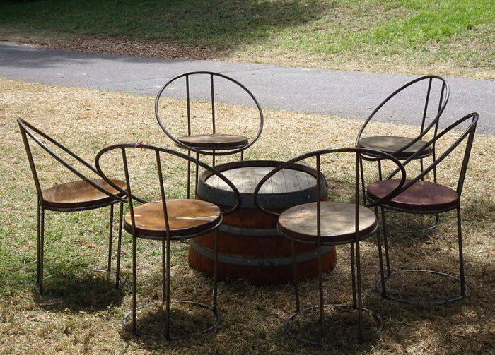 round seats made from barrel parts are sat around a low table, made from an barrel cut in half
