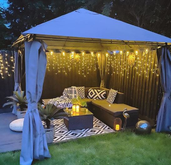 a gazebo with the sides open to reveal a curtain of pretty fairy lights