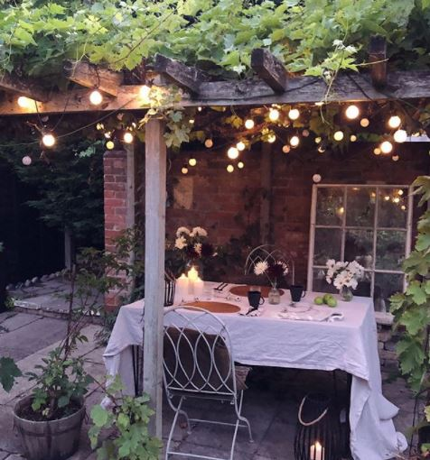a dining area with pretty white tablecloth under a pergola covered with string lights and leafy vines