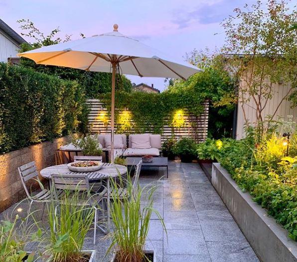 a contemporary patio with subtle garden lighting