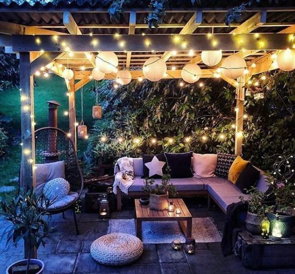 a pergola at night with several kinds of fairy lights and lanterns hanging from the roof