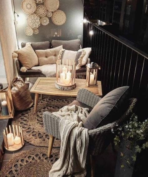 a cosy balcony lit by several clusters of white pillar candles