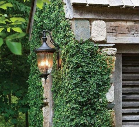 a black metal lantern on the outside of a rustic stone building