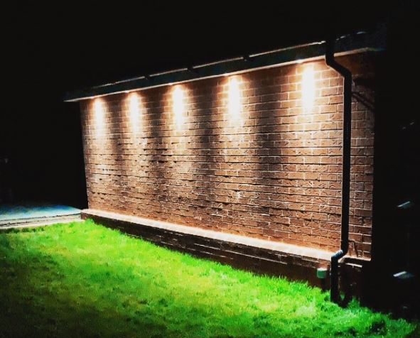 the side of a garage with bright downlighters illuminating the grass below