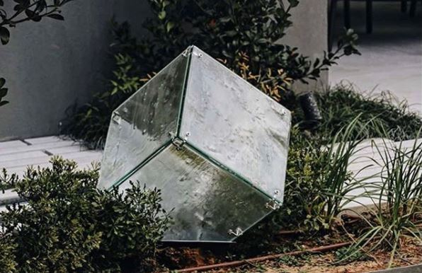 a transparent, cube shaped light in a flower bed