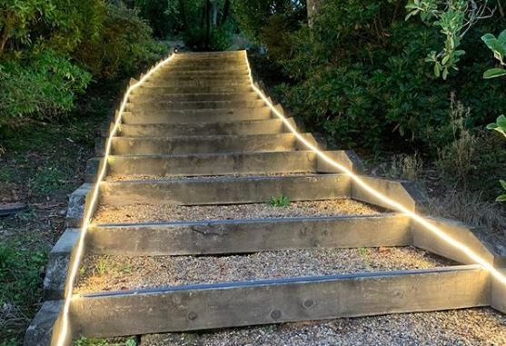 a set of shallow gravel garden steps with LED cable lighting running up either side