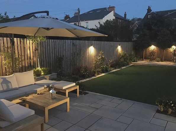 a manicured garden with a contemporary patio and stylish lights along the fences