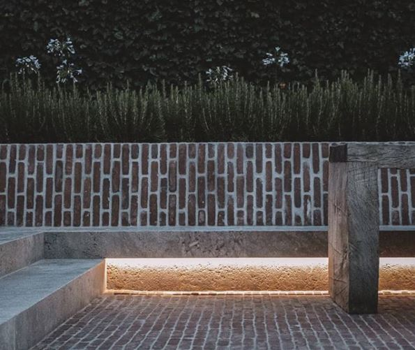 a concrete bench in front of a weathered brick wall on a weathered brick patio