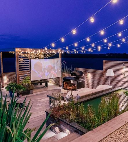 a tidy garden deck over two levels, with pretty garden pond lighting and home cinema screen