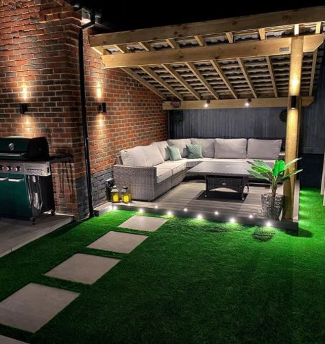 a garden deck under a pergola with spotlights and accent lights