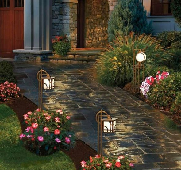 Japanese inspired stake lights between flowering shrubs along a stone path