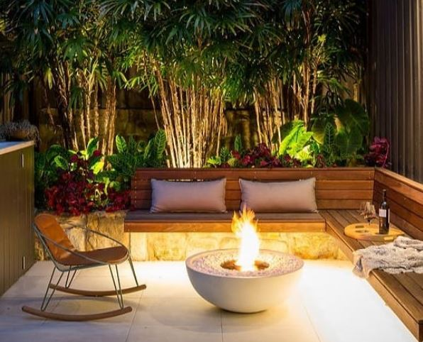 deck lighting ideas - a small space with a fire pit and uplighters in the flower beds