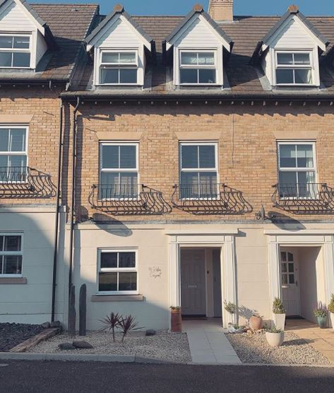 front garden ideas - a gravel garden with sand-coloured pebbles that complement the cream of the house