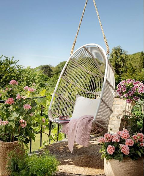 A beautiful suspended chair wth a pink blanket, surrounded by flowers