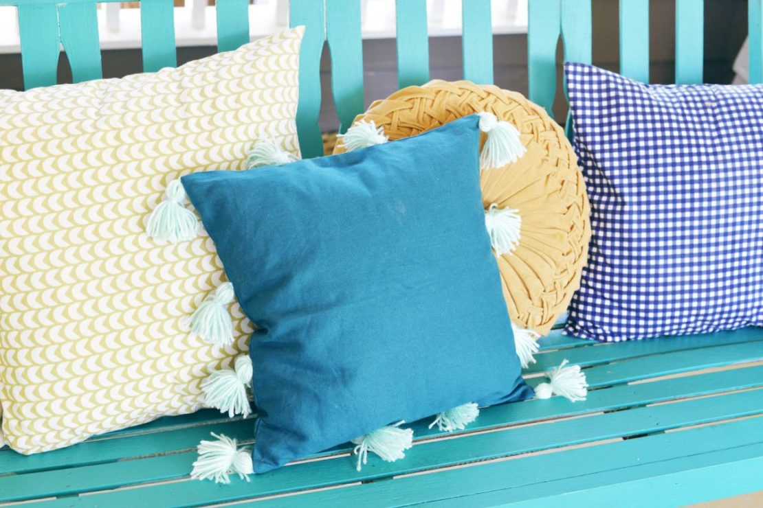 A bench with assorted cushions, including one in blue velvet with pretty white tassles