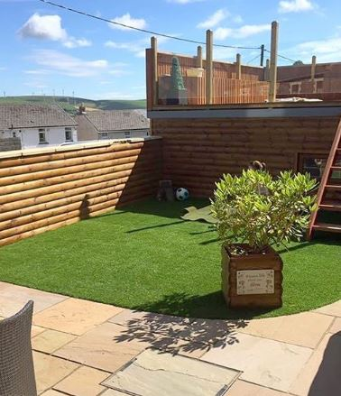 A garden with a corner of artificial grass, the rest is paved and there are wooden steps leading to an upper level.