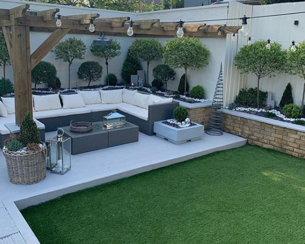 A garden with artificial grass and a white deck with a huge rattan sofa beneath a pergola