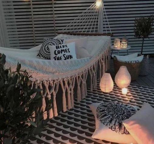 A hammock with tassels and printed cushions surrounded by lanterns and candles