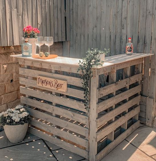 A pallet bar in the corner of a patio, in the same grey as the garden fence. Several potted plants decorate the counter and surrounding floor.