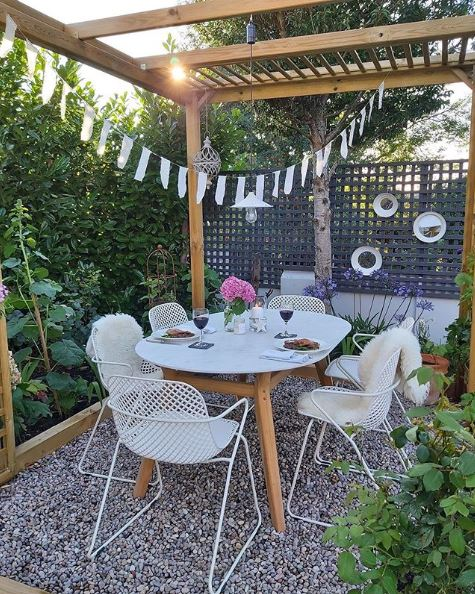 A slender-framed set of dining table and chairs on a gravel patio, under a pergola with festoon lights