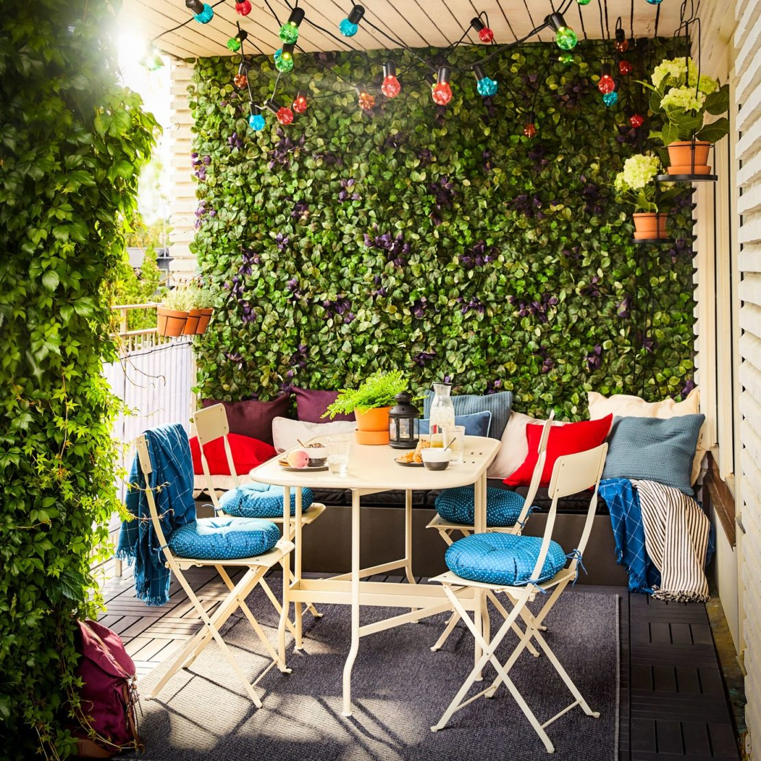 A small balcony with folding chairs and table, coloured string lights and artificial plant tiles covering the walls