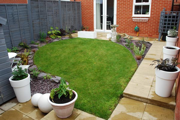 A small garden with a tidy flower bed, lawn and several big white planters