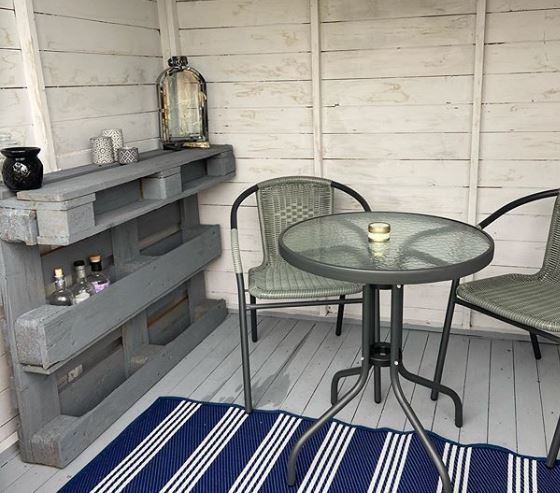 A small shed with table, chairs and a shelf made from a wooden pallet, housing some bottles.