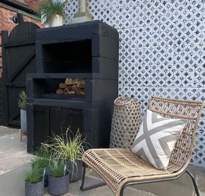 A stylish wood-fired pizza oven surrounded by a wicker chair and pot plants on a patio