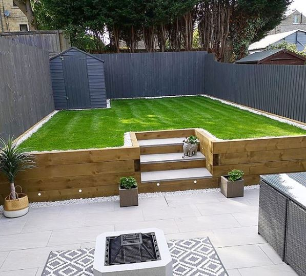 A tidy garden with a patio area and steps leading up to a raised lawn made from AstroTurf