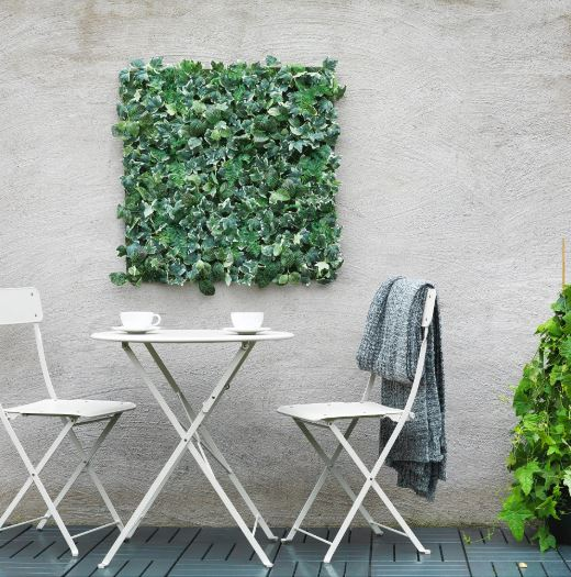 A white bistro set on a deck against a wall with artificial plant tiles