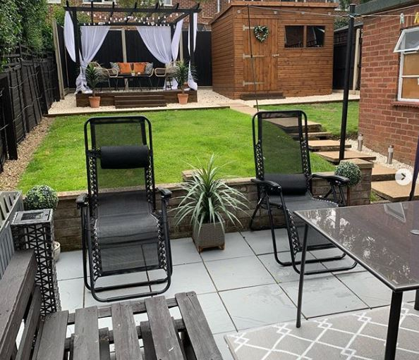 A manicured garden with a pallet bench, reclining loungers, a dining table and outdoor sofa
