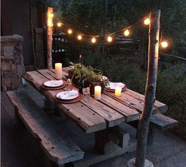 An old, weathered picnic table with place settings and string lights hanging above