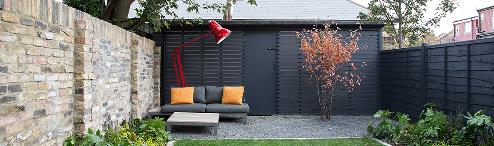 a giant adjustable Anglepoise lamp sits behind a garden sofa on a patio in front of a shed