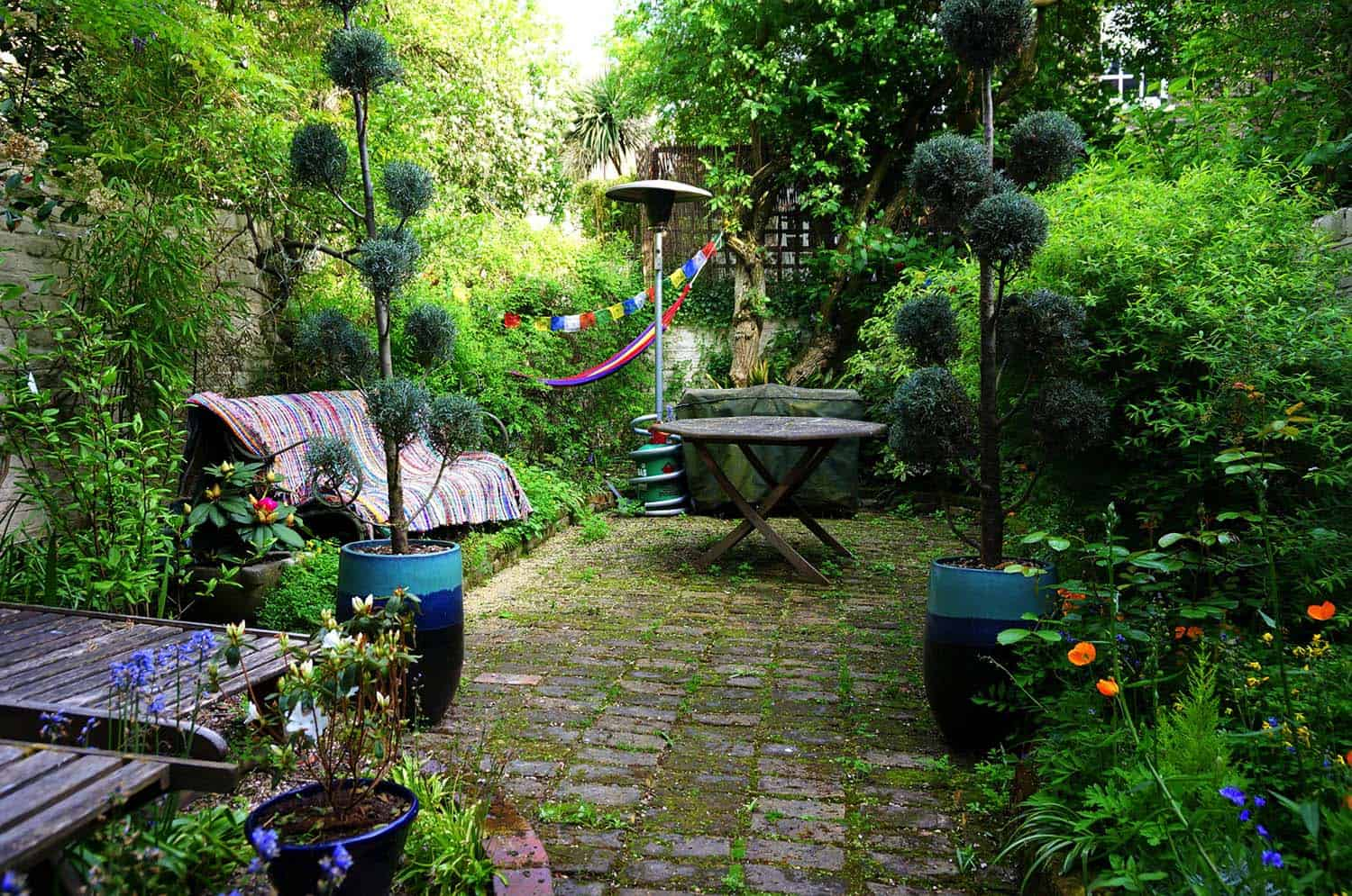 Bohemian garden with mossy cobblestones and slightly overgrown flower beds