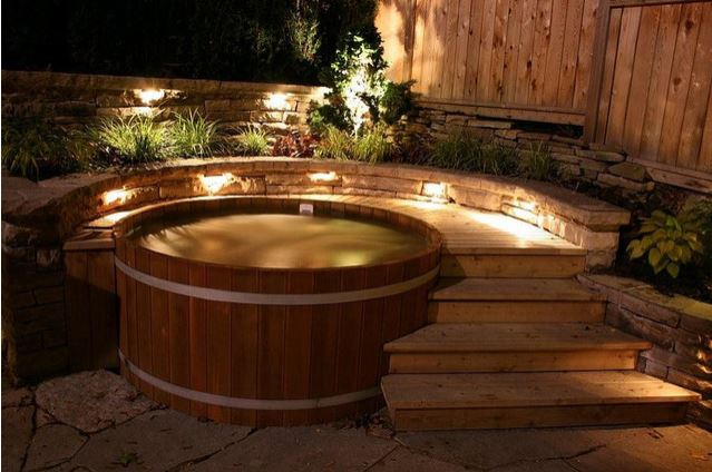 A round wooden hot tub with a curved deck and steps surrounding it