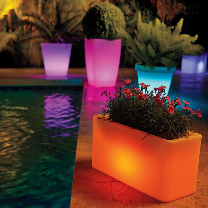 solar-powered planters lit up in various colours around the edge of a pool