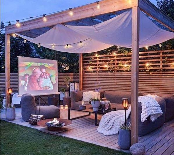 Cosy garden cinema set up under a pergola with festoon lighting